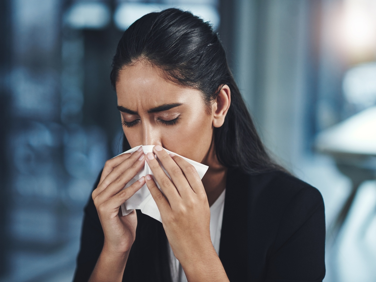 Business woman sneezing
