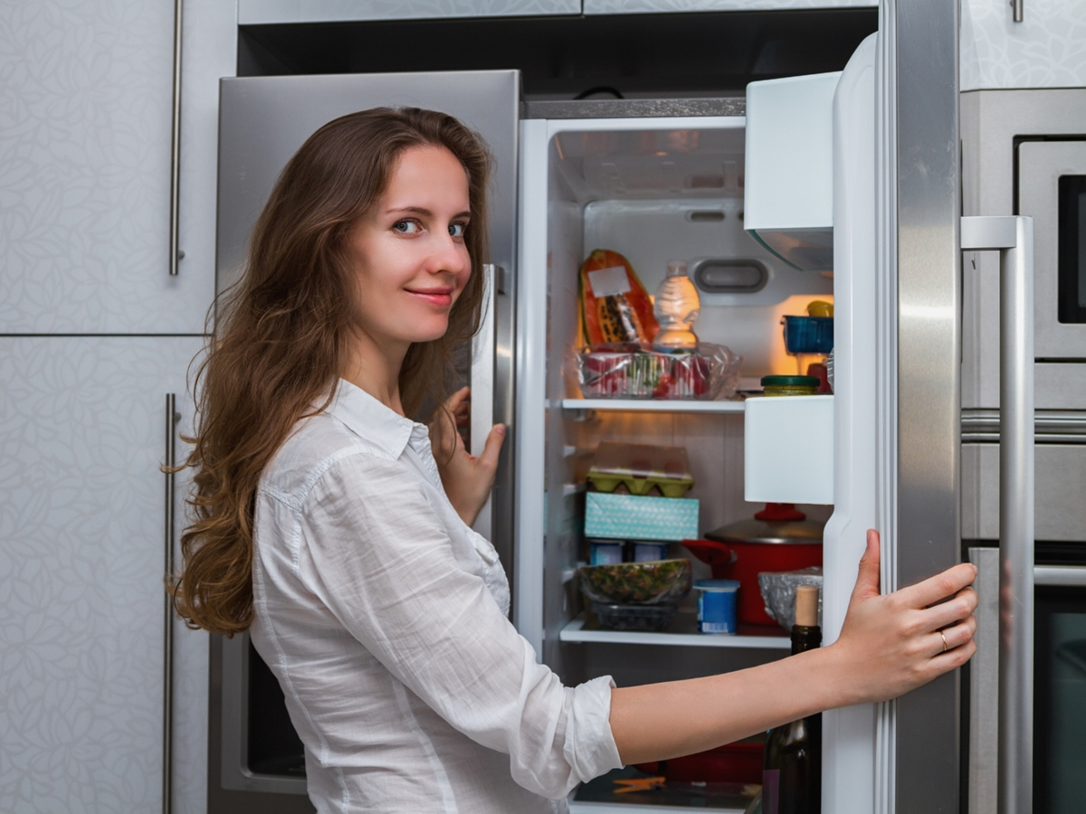 Women standing in front of an open refrigerator