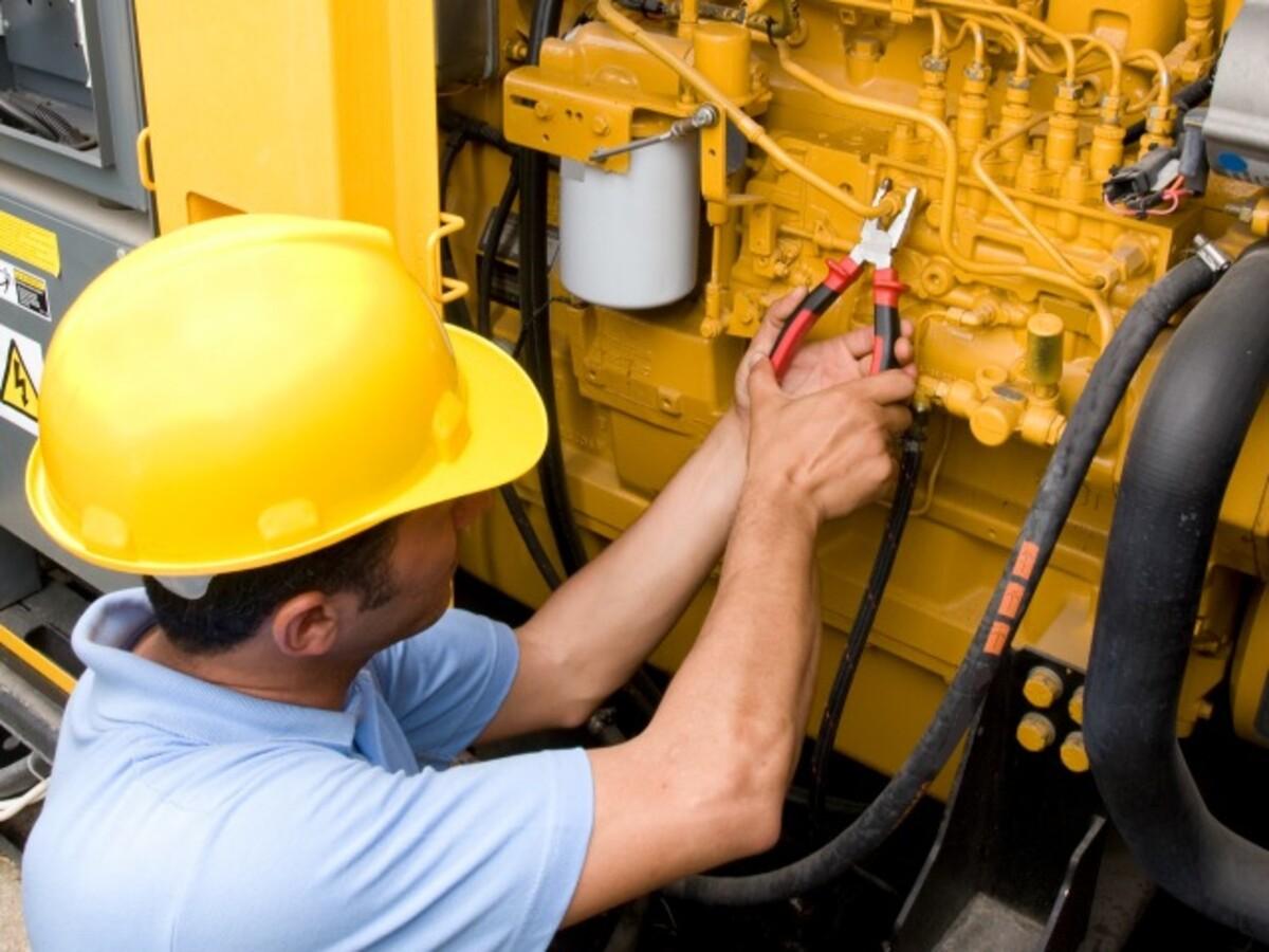Worker in hardhat performing maintenance on generator