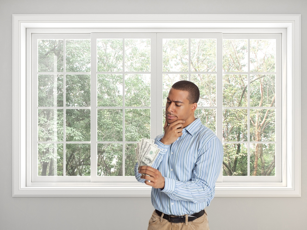 Man standing in front of window looking at money